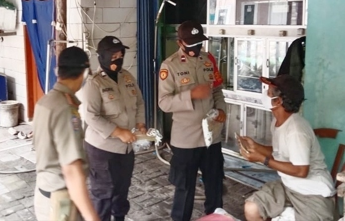 Anggota dan jajaran Polres Kepulauan Seribu membagikan masker ke masyarakat. (Foto: PMJ News).